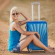 Blonde sitting on suitcases at the side of the road — Stock Photo #52341293