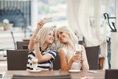 Two girls drink coffee and use the phone — Stock Photo