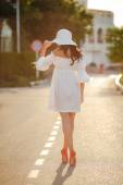 Lonely woman in a hat on an empty road — Stock Photo