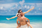 Loving couple having fun on the beach of a tropical ocean. — Stock Photo