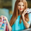 Pretty lady showing credit card in the mall — Stock Photo #54319383