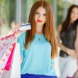 Pretty lady showing credit card in the mall — Stock Photo #54319719