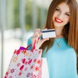 Pretty lady showing credit card in the mall — Stock Photo #54319749