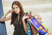 Happy woman shopping and holding bags at the mall — Stock Photo