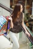 Mujer feliz compras y sosteniendo bolsas en el centro comercial — Foto de Stock