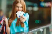 Pretty lady showing credit card in the mall — Stock Photo