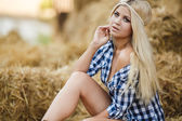 Sexy blonde woman resting on hay in rural areas — Stock Photo