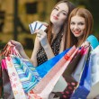 Two women make purchases with credit cards at the mall — Stock Photo #57088869