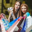Two women make purchases with credit cards at the mall — Stock Photo #57088883