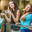 Two women make purchases with credit cards at the mall — Stock Photo #57088889