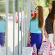 Two cute women view showcases the supermarket. — Stock Photo #57089267