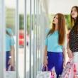 Two cute women view showcases the supermarket. — Stock Photo #57089277