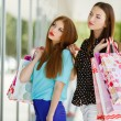 Two cute women view showcases the supermarket. — Stock Photo #57089285