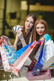 Two women make purchases with credit cards at the mall — Foto de Stock