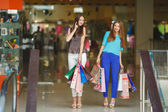 Two young women shop in a big supermarket. — Stock Photo