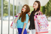 Two cute women view showcases the supermarket. — Stock Photo