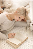 Woman reading a book lying on the sofa. — Stock Photo