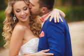 The groom kisses the bride in a green Park in the summer. — Stock Photo