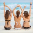 Постер, плакат: Girls in bikinis sunbathing sitting on the beach