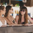 Three beautiful girls in a bar on the beach, on the ocean. — Stock Photo #63760969