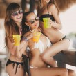 Three beautiful girls in a bar on the beach, on the ocean. — Stock Photo #63761059