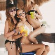 Three beautiful girls in a bar on the beach, on the ocean. — Stock Photo #63761109