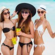 Three girls in hats drinking juice near the sea — Stock Photo #63761169
