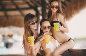 Three beautiful girls in a bar on the beach, on the ocean. — Stock Photo