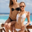 Постер, плакат: Beautiful girls in bikini relaxing on the beach on the ocean background