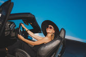 Portrait of a young lady in the car in a big black hat. — Stock Photo