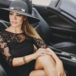 Portrait of a young lady in the car in a big black hat. — Stock Photo #64512419