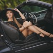Portrait of a young lady in the car in a big black hat. — Stock Photo #64512423