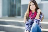 Portrait of a beautiful young woman sitting on the steps. — Stock Photo