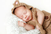 Photo of a newborn baby curled up sleeping on a blanket — Fotografia Stock