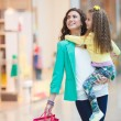 Young mother and her daughter doing shopping together — Stock Photo #65723487
