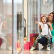 Young mother and her daughter doing shopping together — Stock Photo #65723525