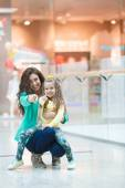 Young mother and her daughter doing shopping together — Stock Photo
