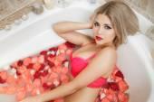 Žena, koupání ve vaně plné růží. — Stock fotografie