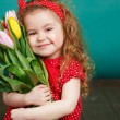 Beautiful little girl with a big bouquet of tulips. — Stock Photo #66876313