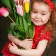 Beautiful little girl with a big bouquet of tulips. — Stock Photo #66876333