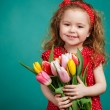 Beautiful little girl with a big bouquet of tulips. — Stock Photo #66876345