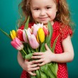 Beautiful little girl with a big bouquet of tulips. — Stock Photo #66876349