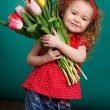 Beautiful little girl with a big bouquet of tulips. — Stock Photo #66876373