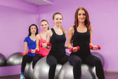 The girls are preparing to perform a set of exercises with a large ball for fitness. — Stock Photo