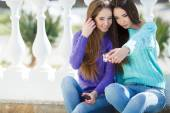 Two beautiful girlfriends watching pictures and listening to music on their smartphones. — Stock Photo