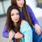 Urban portrait of two beautiful girlfriends. — Stock Photo #69815551