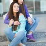 Urban portrait of two beautiful girlfriends. — Stock Photo #69815563
