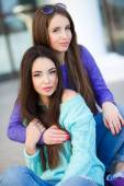 Urban portrait of two beautiful girlfriends. — Stock Photo