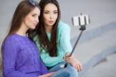 Two young attractive women are photographed with a smartphone in the streets. — Stock Photo