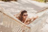 Portrait of a sexy girl in a bikini lying on a hammock — Stock Photo